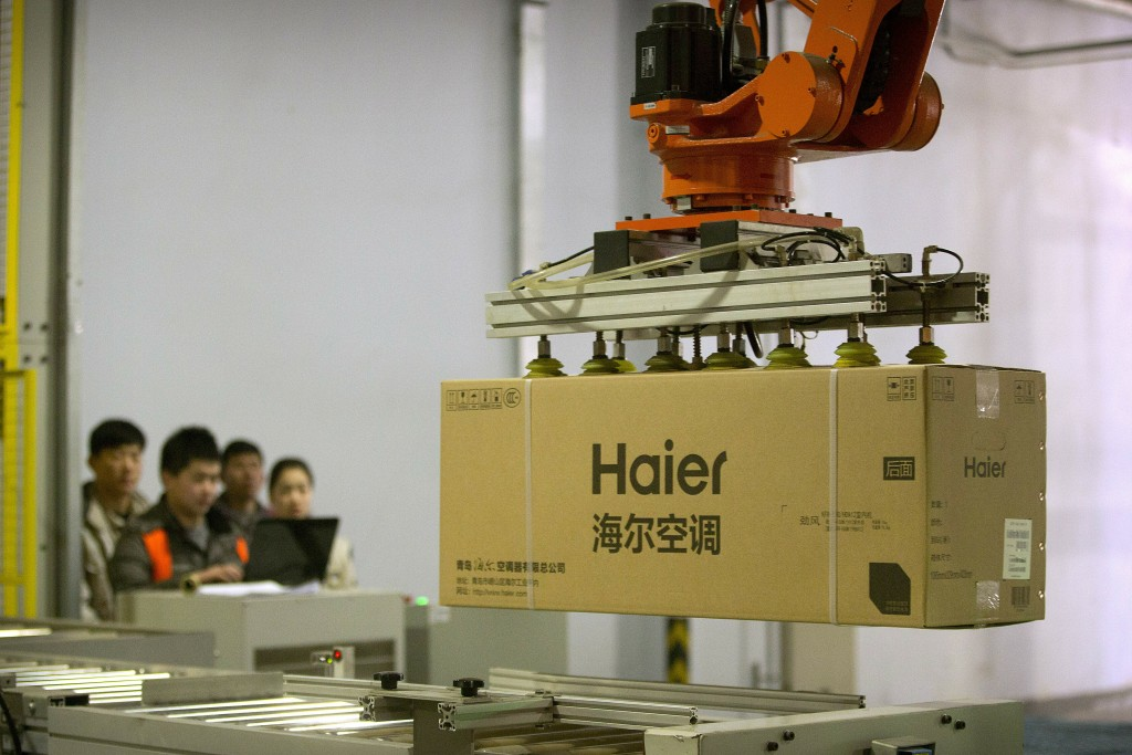 FILE - In this Feb. 24, 2017, file photo, factory workers watch as a machine uses suction to lift a box containing an air conditioner at a Haier facto...