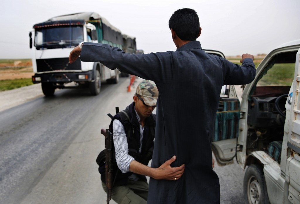 In this March 28, 2018 photo, a Kurdish policeman checks an Arab Syrian man at a checkpoint controlled by The U.S.-backed Syrian Democratic Forces, SD...