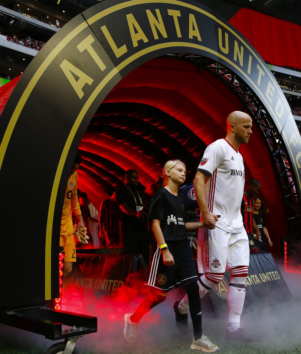 Toronto FC's Michael Bradley walks onto the field with a young fan before the team's MLS soccer match against Atlanta United in Atlanta on Wednesday, ...