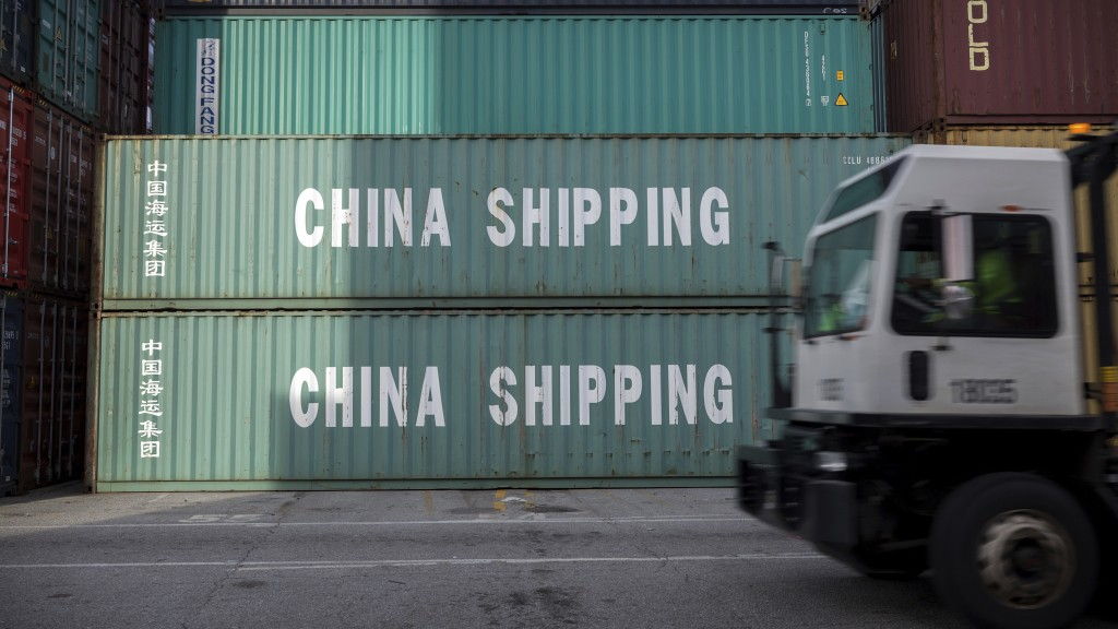 FILE- In this July 5, 2018, file photo, a jockey truck passes a stack of 40-foot China Shipping containers at the Port of Savannah in Savannah, Ga. Fo...