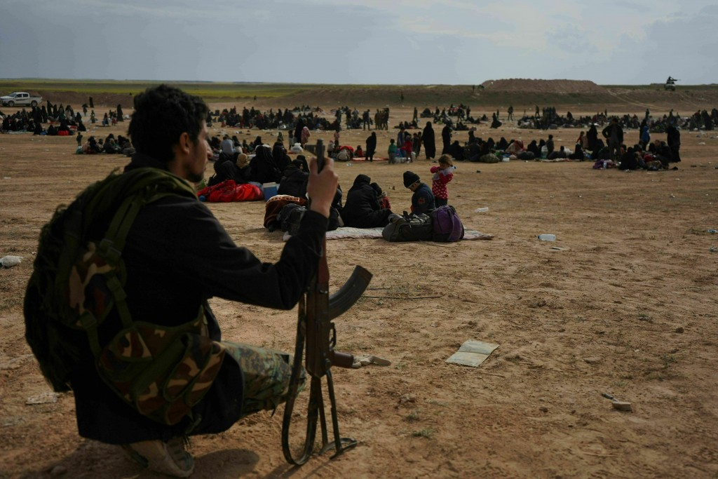 FILE -- In this March 5, 2019 file photo, a member of U.S.-backed Syrian Democratic Forces (SDF) watches over people who were evacuated out of the las...