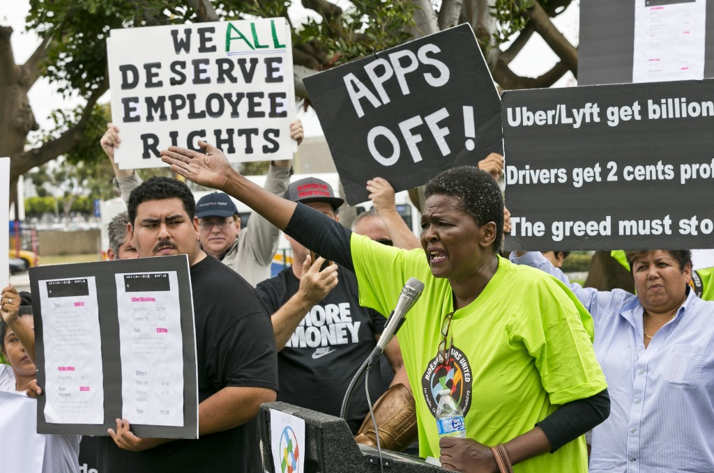 Uber driver Estaphanie St. Just joins drivers for ride-hailing giants Uber and Lyft, as they hold a rally at a park near Los Angeles International Air...
