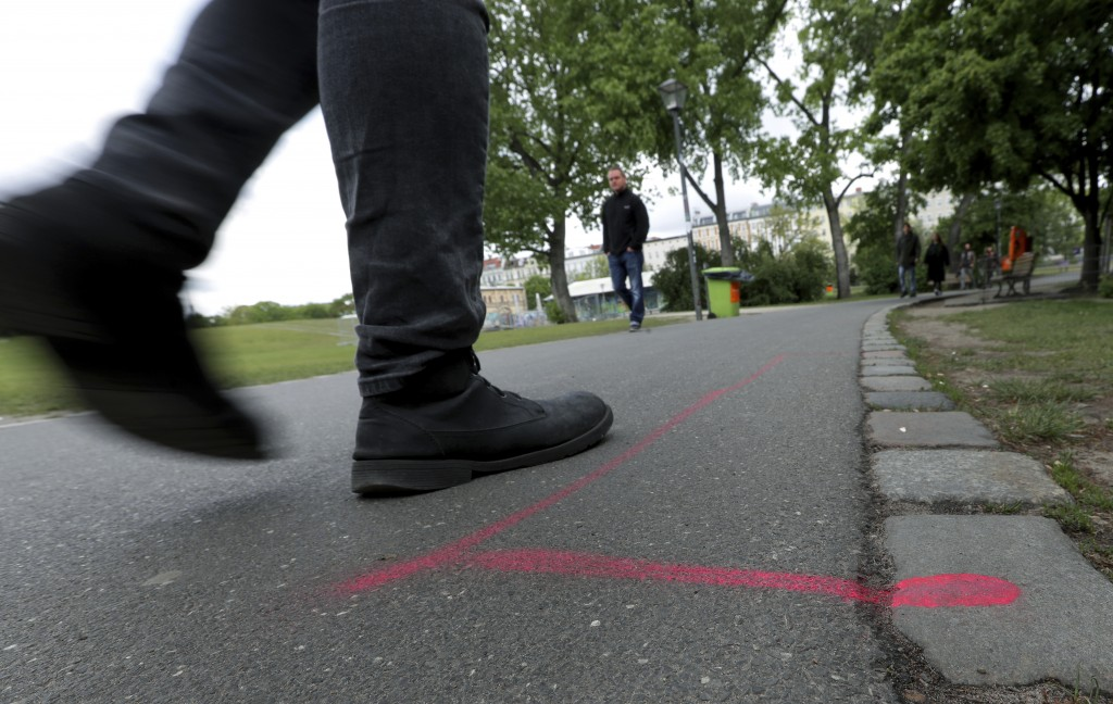 A man walks past a so called 'Drug Dealer Area' next to a traffic training course for kids at the public Goerlitzer Park in Berlin, Germany, Thursday,...