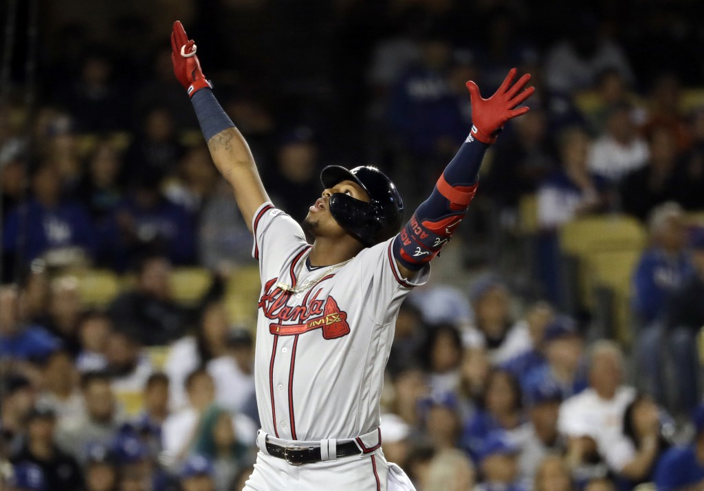 Atlanta Braves' Ronald Acuna Jr. celebrates at home plate after hitting a two-run home run against the Los Angeles Dodgers during the fourth inning of...