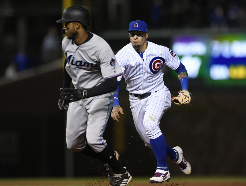 Chicago Cubs shortstop Javier Baez right, chases Miami Marlins' Rosell Herrera during a rundown between second and first during the 10th inning of a b