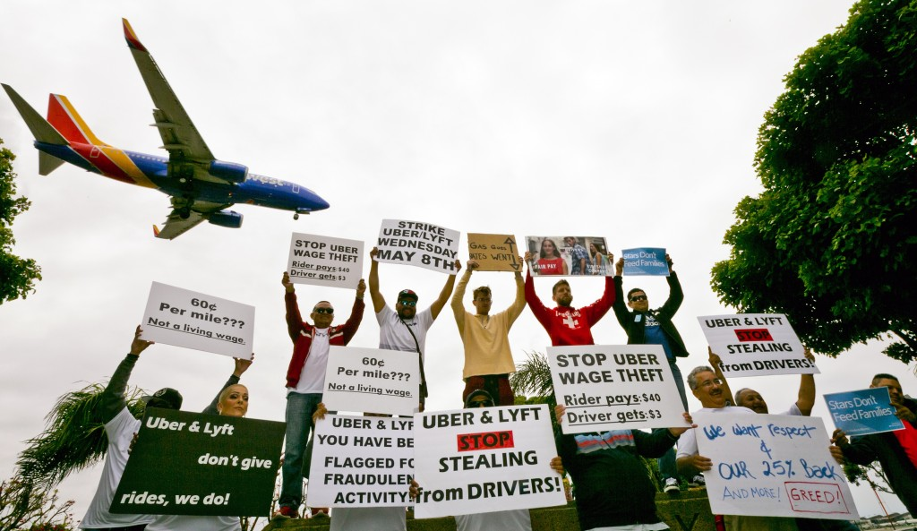 Drivers for ride-hailing giants Uber and Lyft hold a rally at a park near Los Angeles International Airport, Wednesday, May, 8, 2019, in Los Angeles. ...