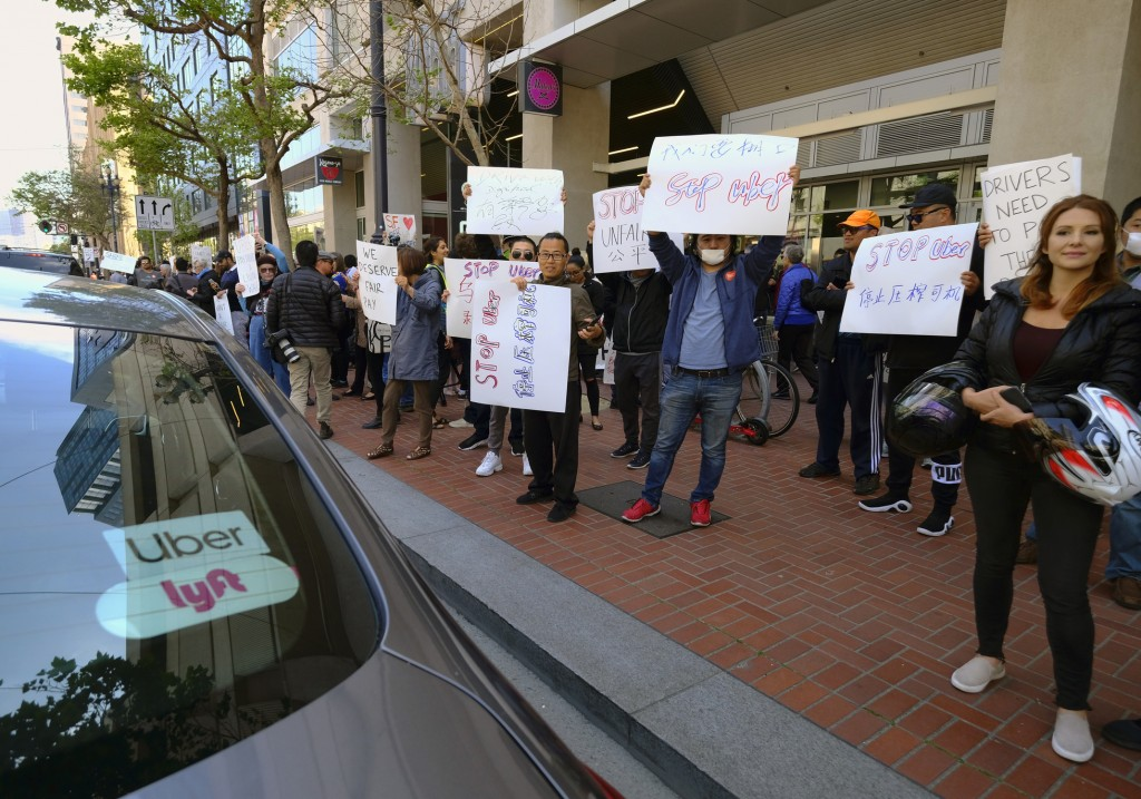 Uber and Lyft drivers carry signs during a demonstration outside of Uber headquarters Wednesday, May 8, 2019, in San Francisco. As Uber executives lur...