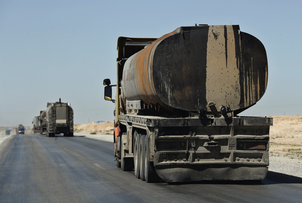 In this April 4, 2018 photo, a convoy of oil trucks moves fuel produced in Kurdish-held areas, in Hassakeh province, Syria. The U.S.-backed Syrian Dem