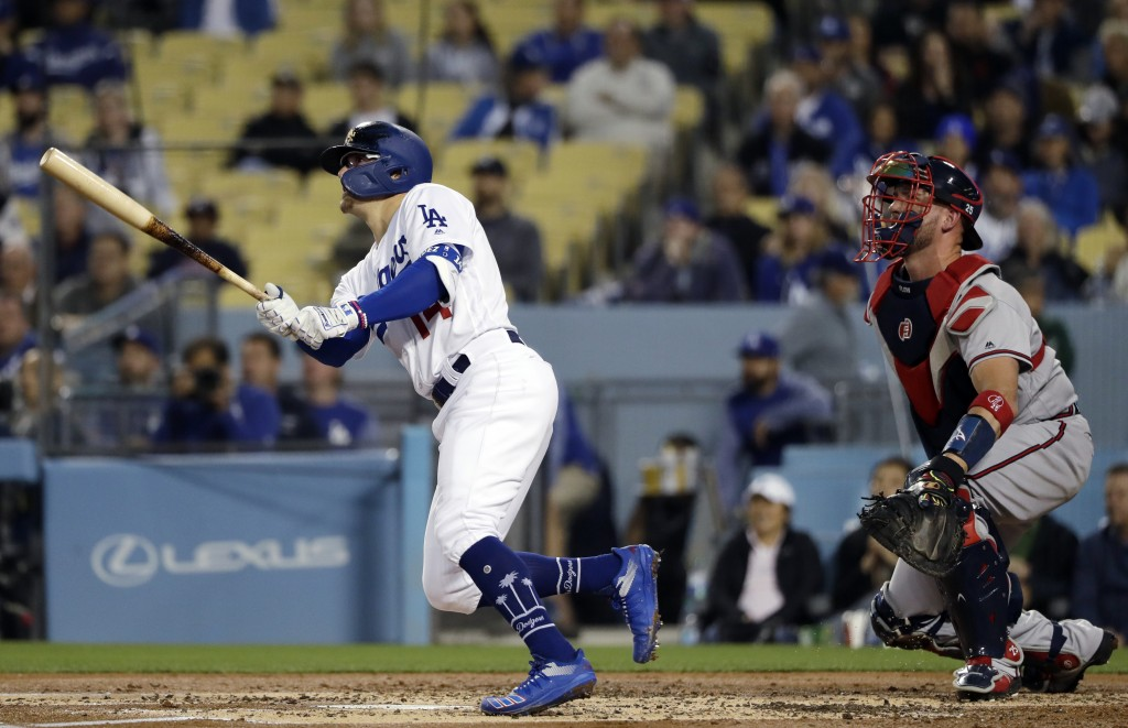 Los Angeles Dodgers' Enrique Hernandez, left, watches his two-run home run against the Atlanta Braves during the second inning of a baseball game Wedn...