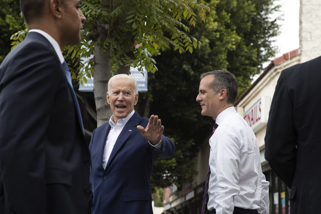 Former vice president and Democratic presidential candidate Joe Biden, left, waves toward members of the media as he and Los Angeles Mayor Eric Garcet...