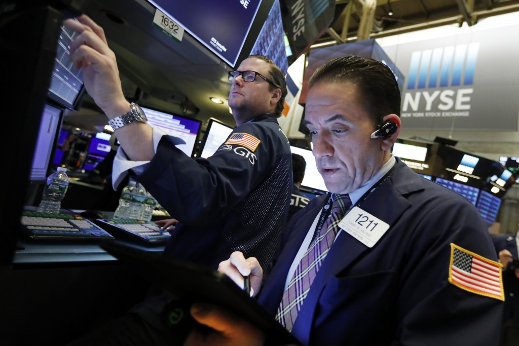 FILE- In this April 2, 2019, file photo specialist Gregg Maloney, left, and trader Tommy Kalikas work on the floor of the New York Stock Exchange. The...