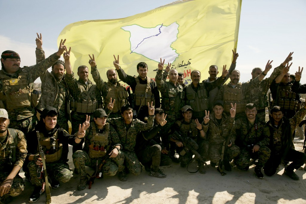 FILE - In this March 23, 2019 file photo, U.S.-backed Syrian Democratic Forces (SDF) fighters pose for a photo in Baghouz, Syria, after the SDF declar...