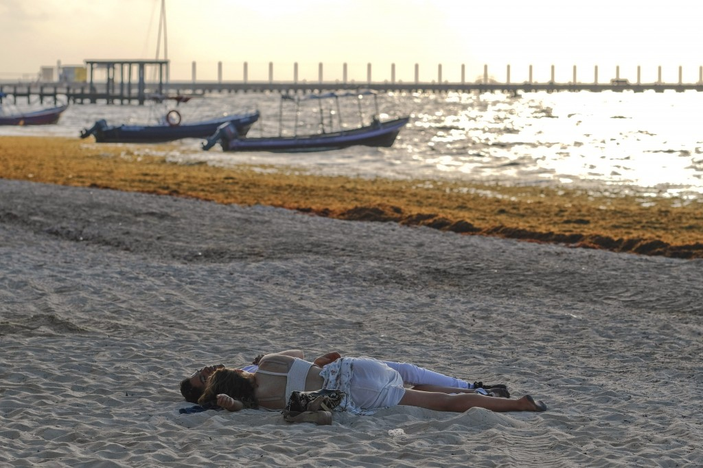 A couple sleeps on the sand on the beach where sargassum seaweed is present in Playa del Carmen, Mexico, at sunrise Wednesday, May 8, 2019. Tourists a...