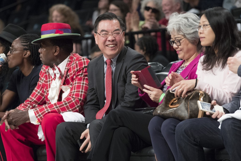 Huang Ping, center, China's consul general in New York, watches a WNBA exhibition basketball game between the New York Liberty and China, Thursday, Ma...