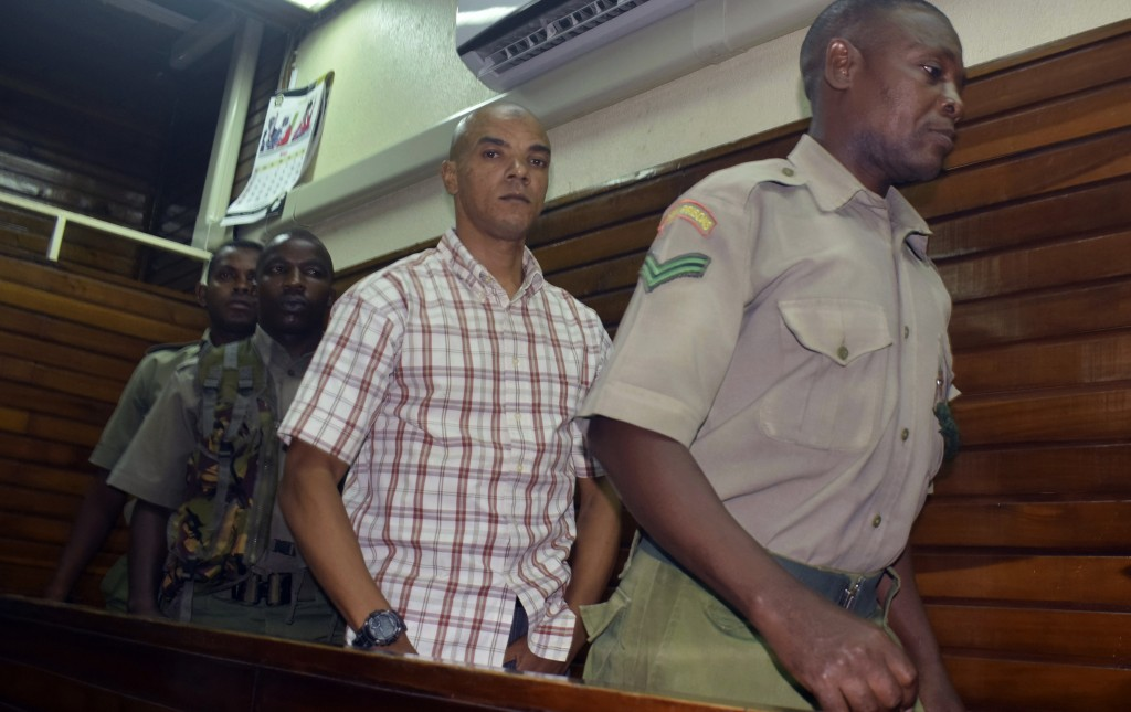 Guarded by heavy security, British suspect Jermaine Grant, centre, walks out of a Mombasa court after being sentenced, in Mombasa, Kenya, Thursday, Ma...