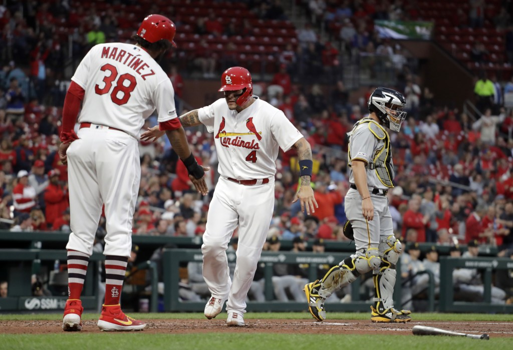 St. Louis Cardinals' Yadier Molina (4) and Jose Martinez (38) celebrate after scoring as Pittsburgh Pirates catcher Francisco Cervelli stands in the b...