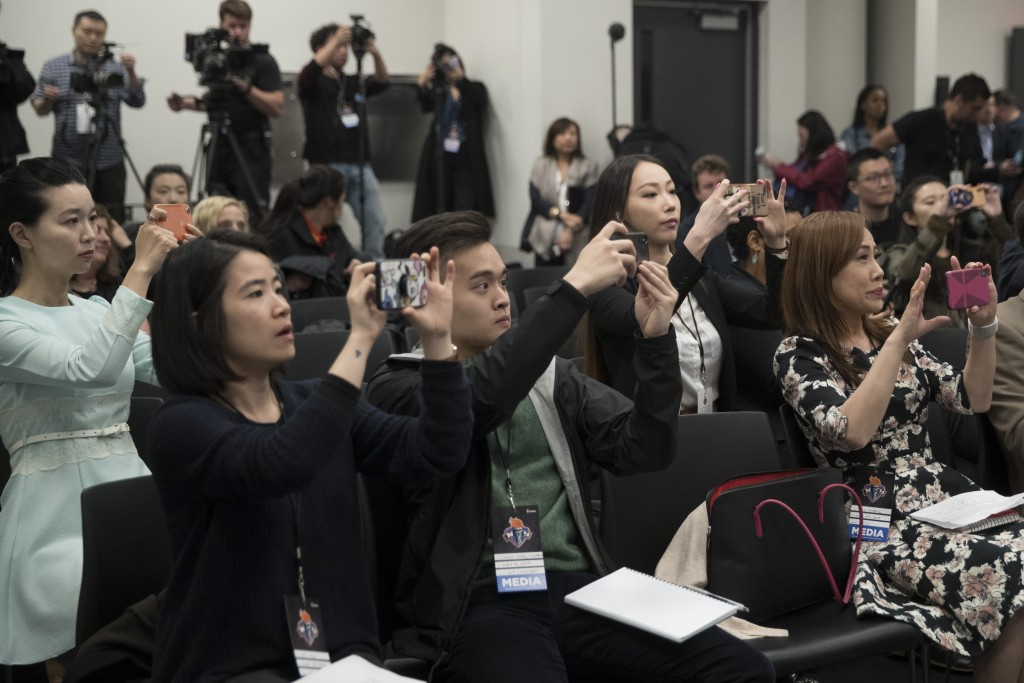 Members of the Chinese media take images and video of the New York Liberty's new owner, Joe Tsai, during a news conference before a WNBA exhibition ba