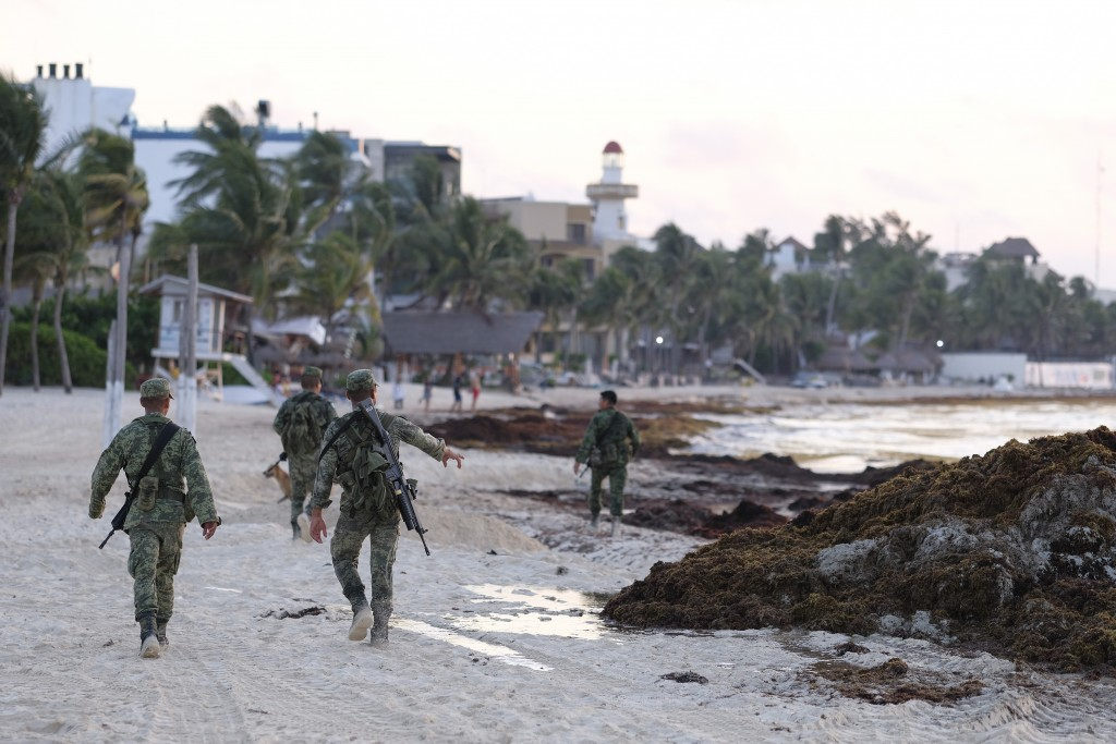 Soldiers walk the beach covered with sargassum seaweed in Playa del Carmen, Mexico, Wednesday, May 8, 2019. The U.S. Gulf coast got hit in 2014 and th...