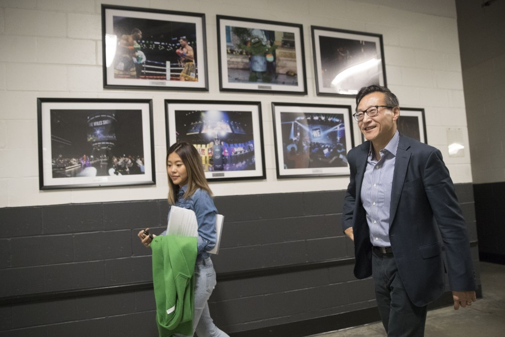 The New York Liberty's new owner, Joe Tsai, right, walks through Barclays Center as he leaves a news conference before a WNBA exhibition basketball ga