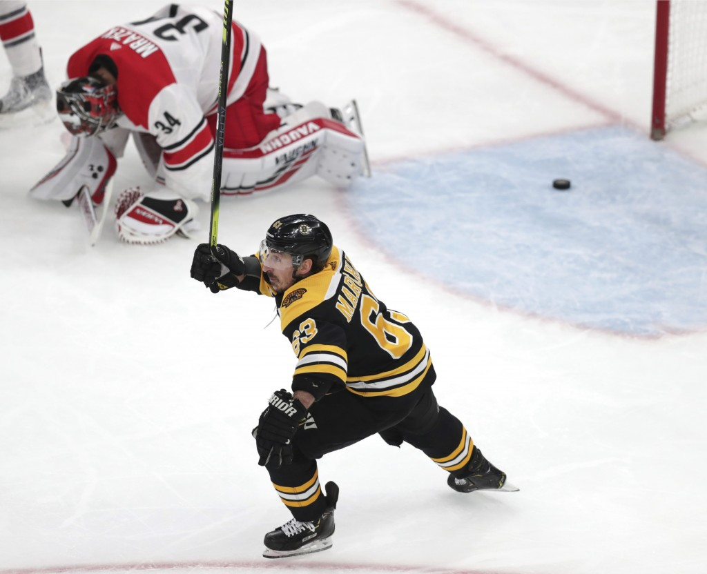 Boston Bruins' Brad Marchand (63) raises his stick as Carolina Hurricanes goaltender Petr Mrazek (34), of the Czech Republic, drops to the ice after a