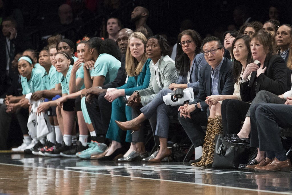 The New York Liberty's new owner, Joe Tsai, third from right, and his wife, Clara Wu Tsai, second from right, watch from next to the Liberty bench dur...