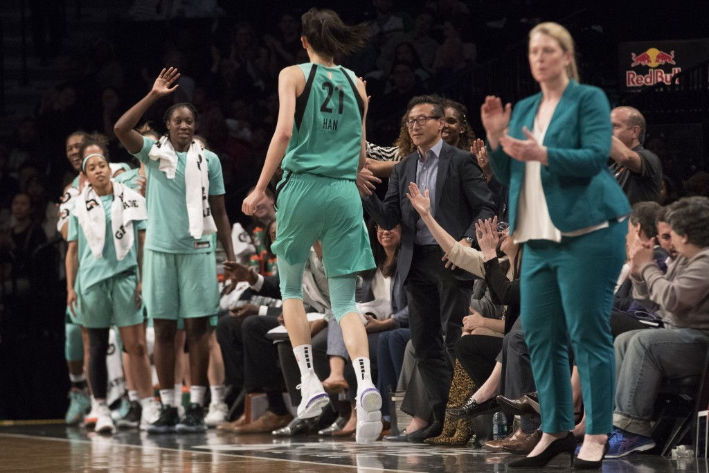 The New York Liberty's new owner, Joe Tsai, second from right, greets center Han Xu (21) as she returns to the bench during the second half of the tea