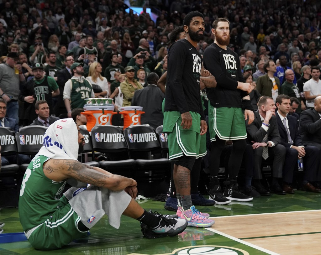 Boston Celtics' Kyrie Irving stands at the bench with teammates Marcus Morris, left, and Aron Baynes, right, during the second half of Game 5 of a sec...