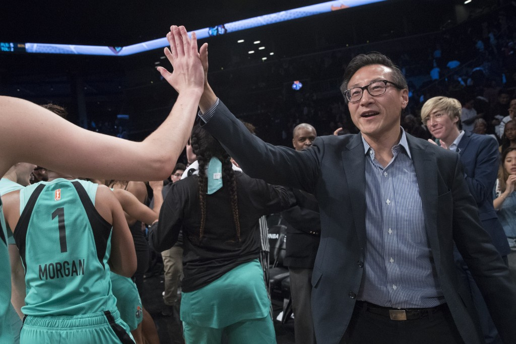 The New York Liberty's new owner, Joe Tsai, right, high-fives the Liberty players as they arrive at the bench at the end of a WNBA exhibition basketba...