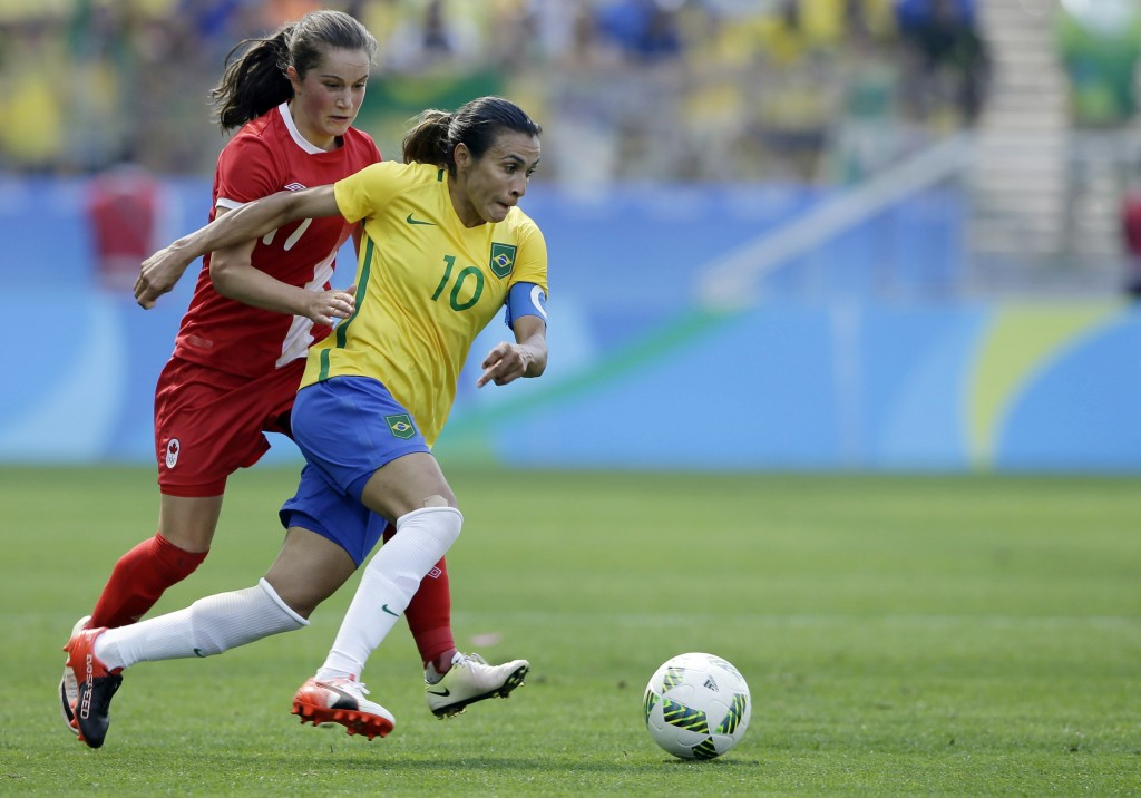 FILE - In this Aug. 19, 2016, file photo, Brazil's Marta, left, dribbles past Canada's Jessie Fleming during the bronze medal women' soccer match at t