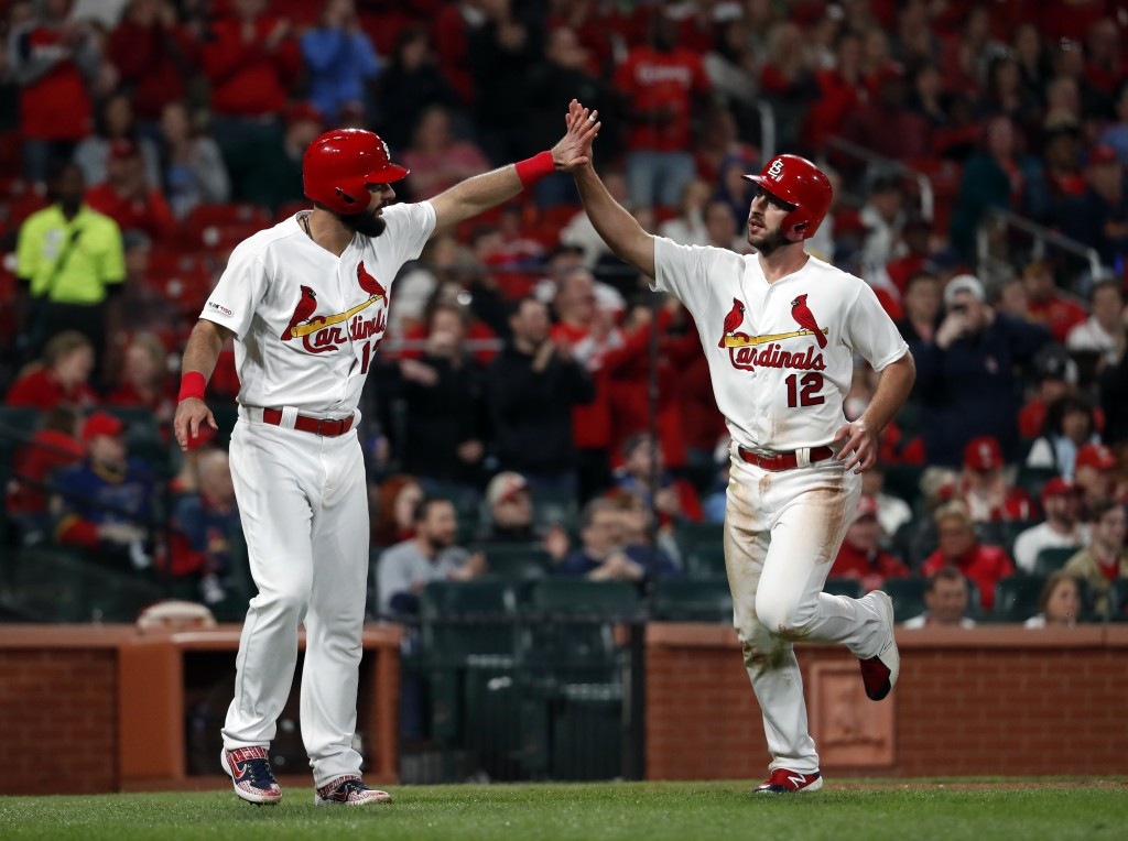 St. Louis Cardinals' Matt Carpenter and Paul DeJong (12) celebrate after scoring on a three-run double by Marcell Ozuna during the sixth inning of a b...