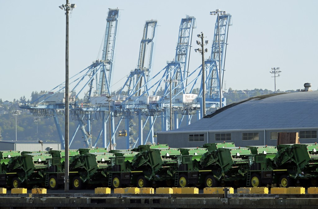 FILE - In this May 10, 2019, file photo John Deere Agricultural machinery made by Deere & Company sits staged for transport near cranes at the Port of...