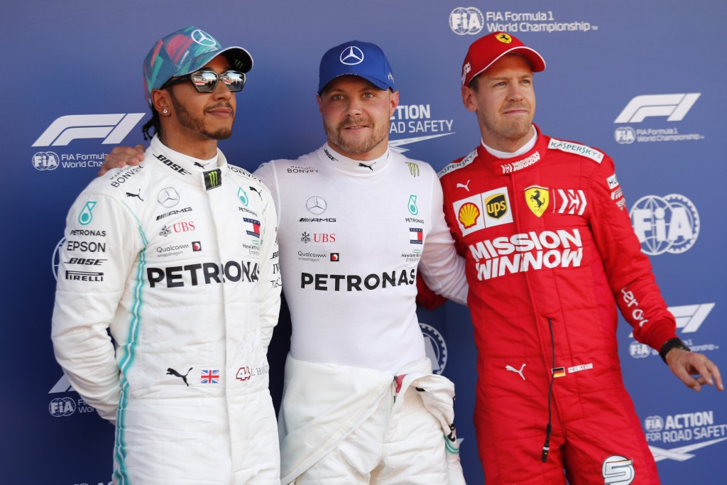 Mercedes driver Valtteri Bottas of Finland, centre, poses with Mercedes driver Lewis Hamilton of Britain, left and Ferrari driver Sebastian Vettel of