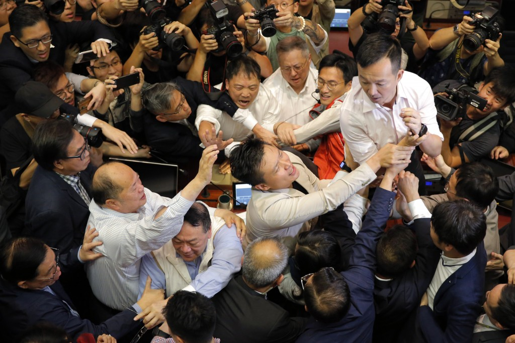In this Saturday, May 11, 2019, file photo, pro-democracy and pro-Beijing lawmakers scuffle in the chamber at Legislative Council in Hong Kong. Hong K