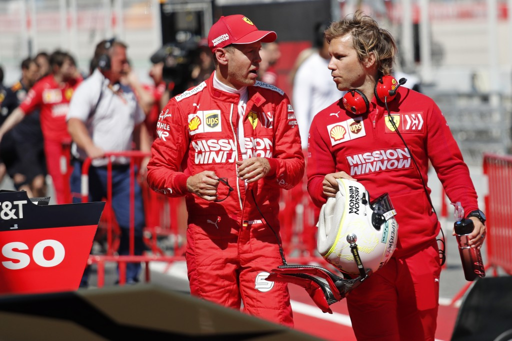 Ferrari driver Sebastian Vettel of Germany, left, speaks with a team member after clocking the 3rd fastest time during the qualifying session at the B