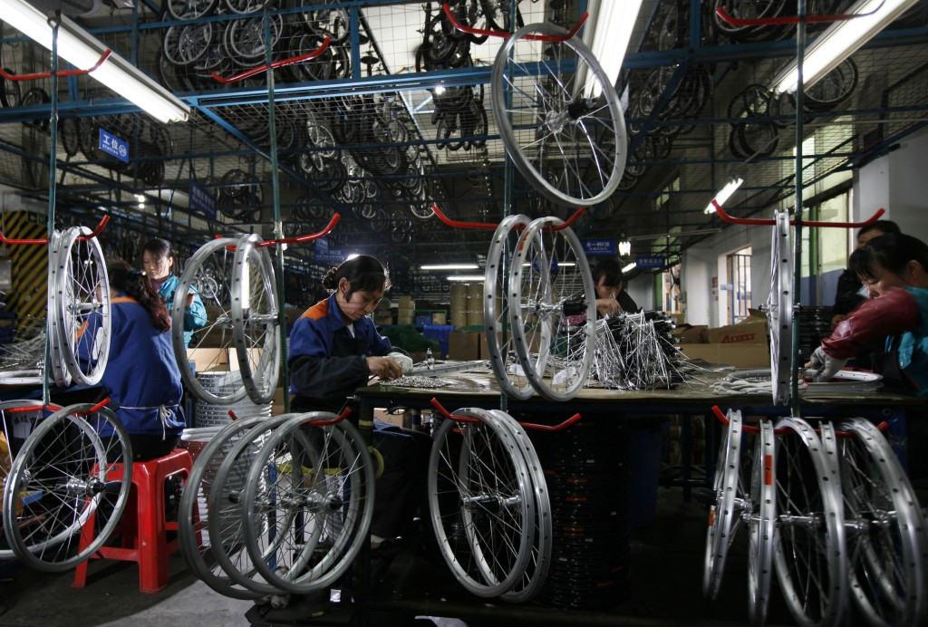 FILE - In this March 4, 2011, file photo, workers from the Dahon, the world's largest maker of folding bicycles, assembles the bicycle wheels in Shenz