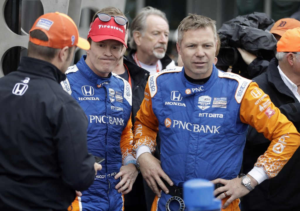 Scott Dixon, second from left, of New Zealand, reacts after finishing second in the Indy GP IndyCar auto race at Indianapolis Motor Speedway, Saturday