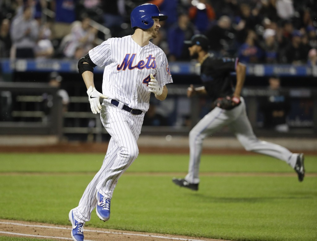 New York Mets' Jacob deGrom, left, runs to first base with an RBI single during the sixth inning of the team's baseball game against the Miami Marlins...