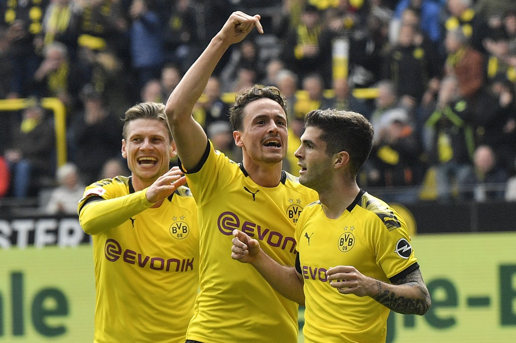 Dortmund's Christian Pulisic celebrates his opening goal with Thomas Delaney and Lukasz Piszczek, from right, during the German Bundesliga soccer matc