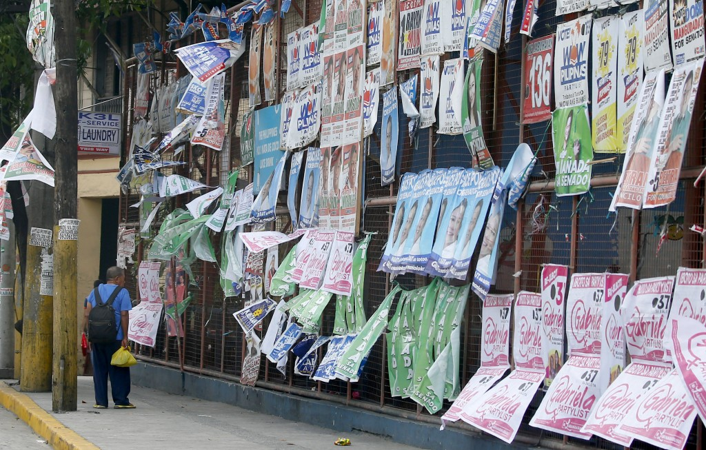 In this Tuesday, May 7, 2019, file photo, a man pauses to look at election posters along a Manila street. President Rodrigo Duterte's name is not on t