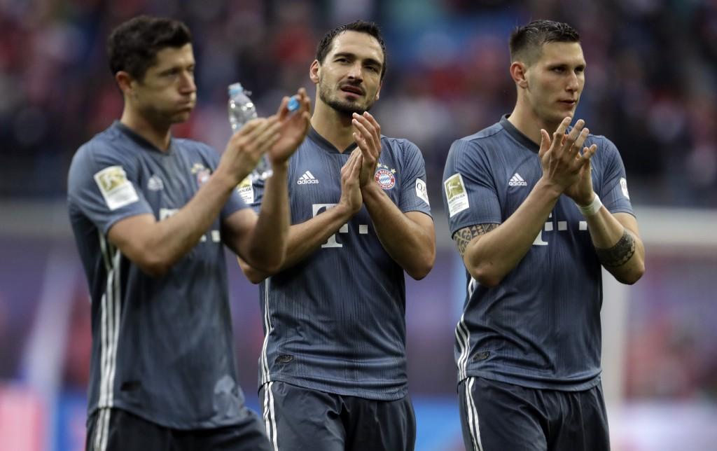 Bayern forward Robert Lewandowski, left, defender Mats Hummels, center and defender Niklas Suele greet supporters at the end of the German Bundesliga
