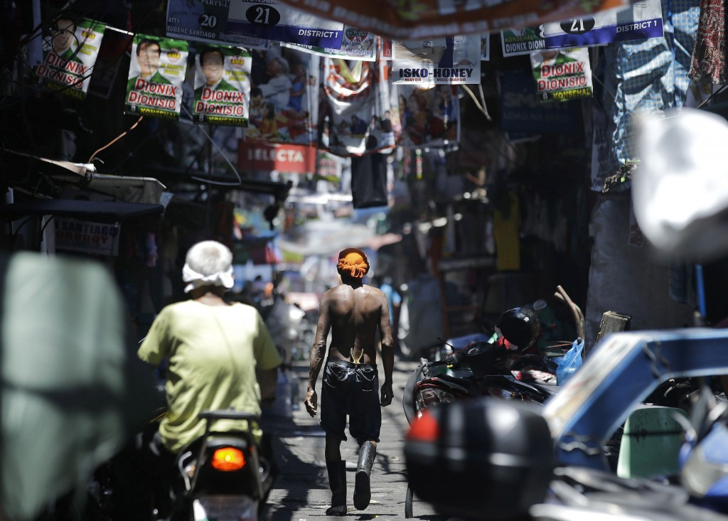 In this Thursday, May 9, 2019, file photo, a man walks past election banners in the slum district of Tondo, Manila, Philippines. Philippine President