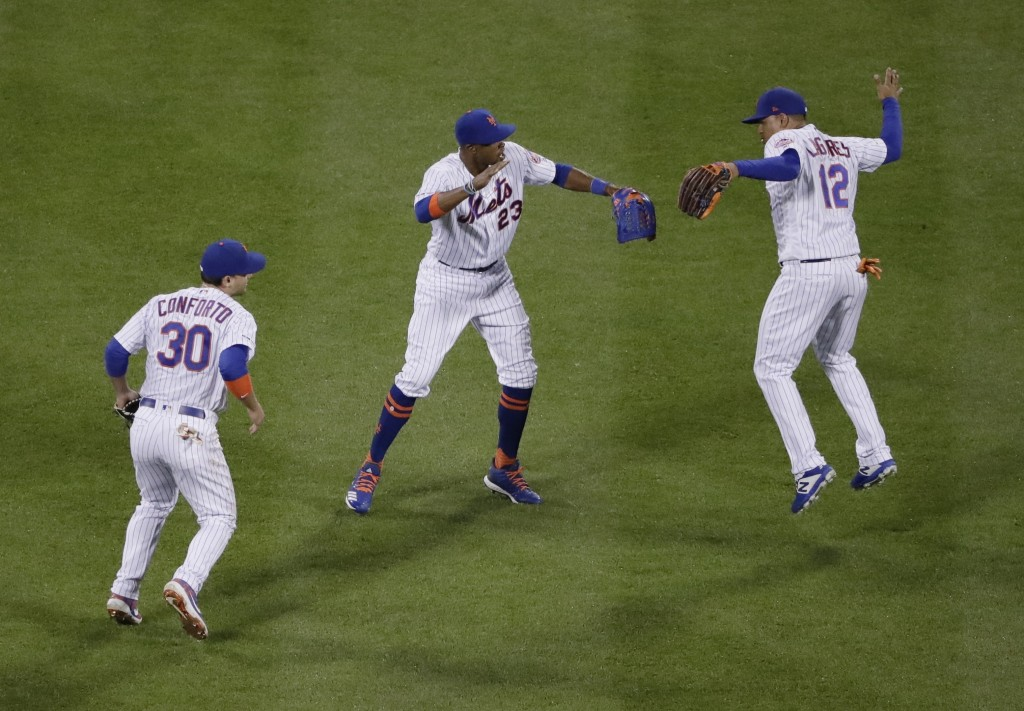 New York Mets' Michael Conforto (30), Keon Broxton (23) and Juan Lagares (12) celebrate after the team's 4-1 win in a baseball game against the Miami ...
