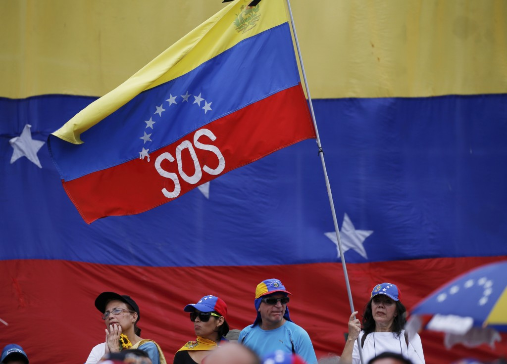 """A supporter of Venezuela's opposition leader and self-proclaimed interim president Juan Guaidó, waves a Venezuelan flag marked with the letters """"SOS"""","""