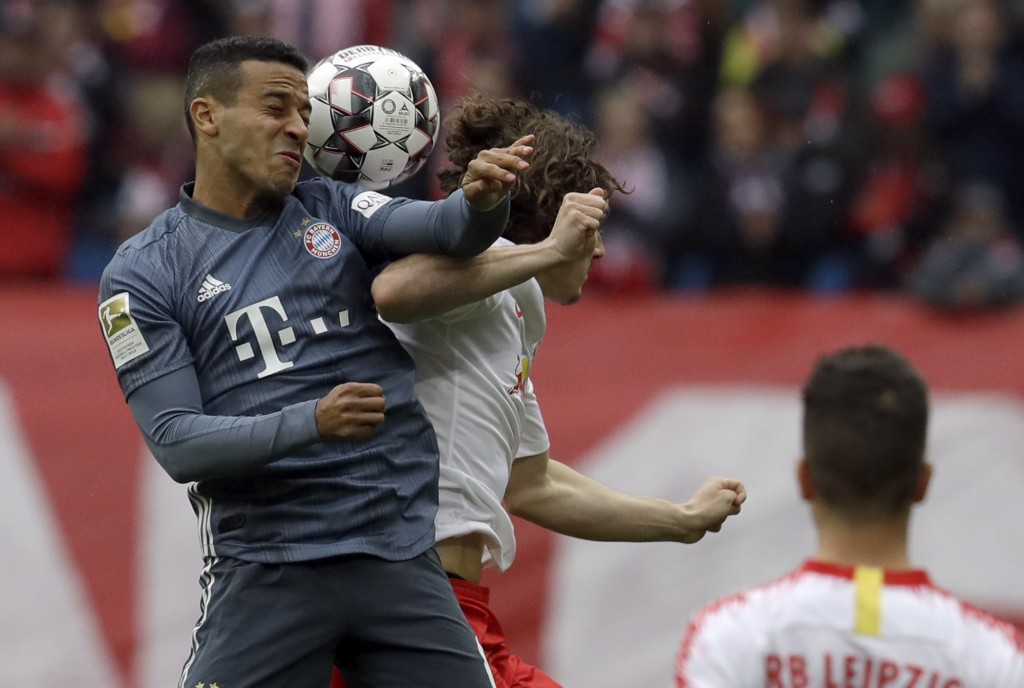 Bayern midfielder Thiago Alcantara, left, jumps for a header with Leipzig's Marcel Sabitzer during the German Bundesliga soccer match between Leipzig