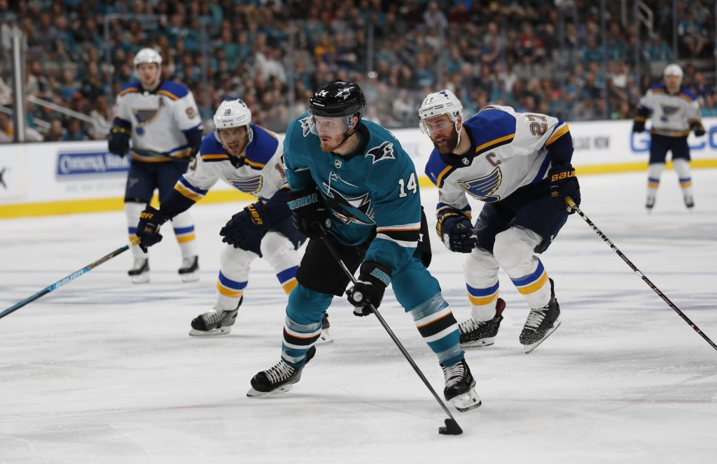San Jose Sharks' Gustav Nyquist (14) moves the puck downice against St. Louis Blues' Brayden Schenn (10) and Alex Pietrangelo (27) in the first period...