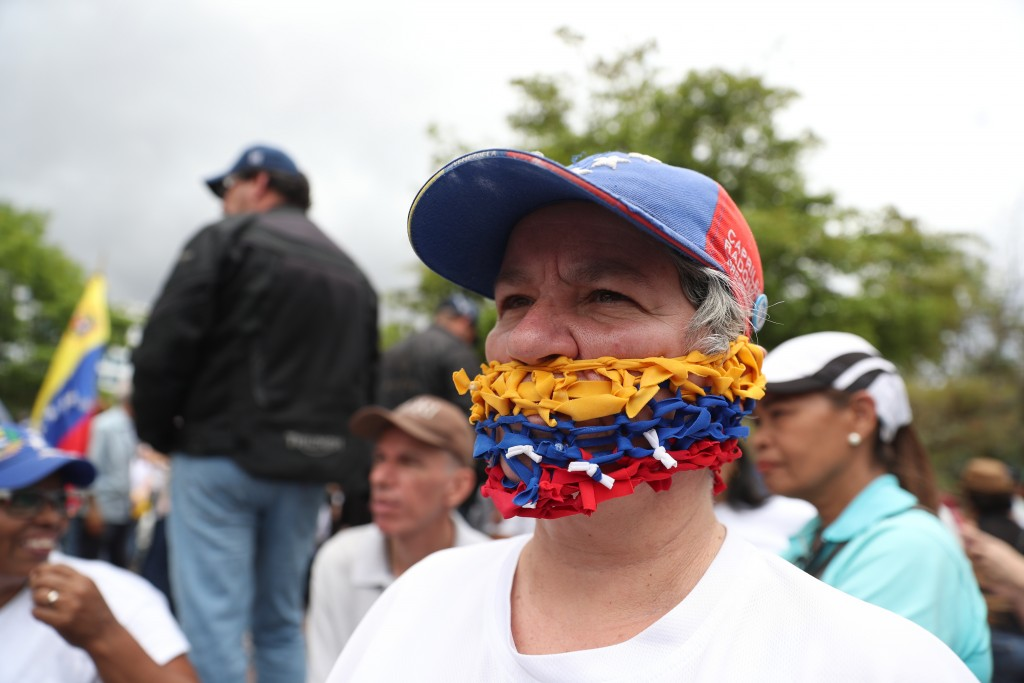 An opponent of the Nicolas Maduro government, his mouth covered with strands representing the national colors of Venezuela, waits for the arrival of o