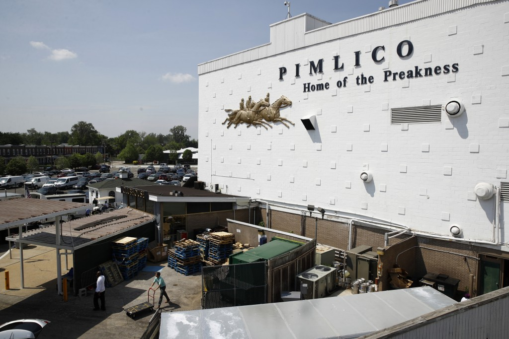 FILE - In this May 15, 2018, file photo, people walk outside of a building at Pimlico Race Course as preparations take place for the Preakness Stakes ...