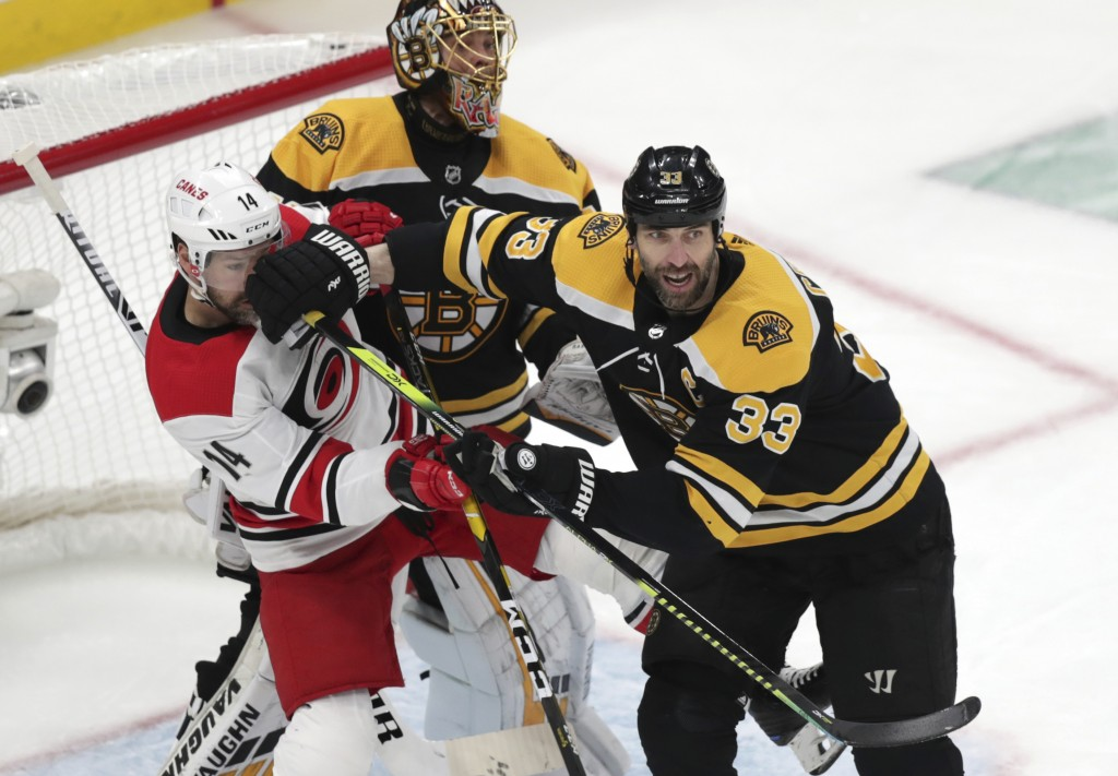 Boston Bruins' Zdeno Chara (33), of Slovakia, pushes Carolina Hurricanes' Justin Williams (14) away from Bruins goalie Tuukka Rask during the first pe...