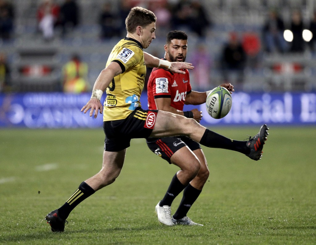 FILE - In this July 28, 2018, file photo, the Hurricanes' flyhalf Beauden Barrett, left, kicks at the ball as the Crusaders' flyhalf Richie Mo'unga wa
