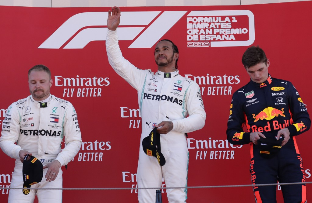 Mercedes driver Lewis Hamilton of Britain, center, celebrates on the podium after winning the Spanish Formula One race, flanked by second place Merced